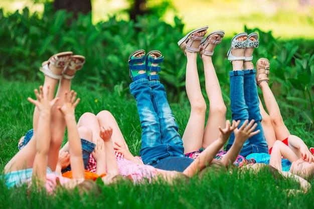 Bambini sdraiati sull'erba verde nel parco in una giornata estiva con le gambe sollevate verso il cielo.