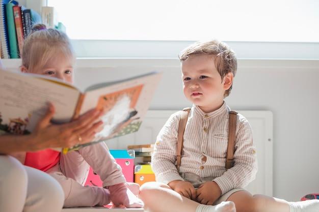Bambini seduti guardando libro
