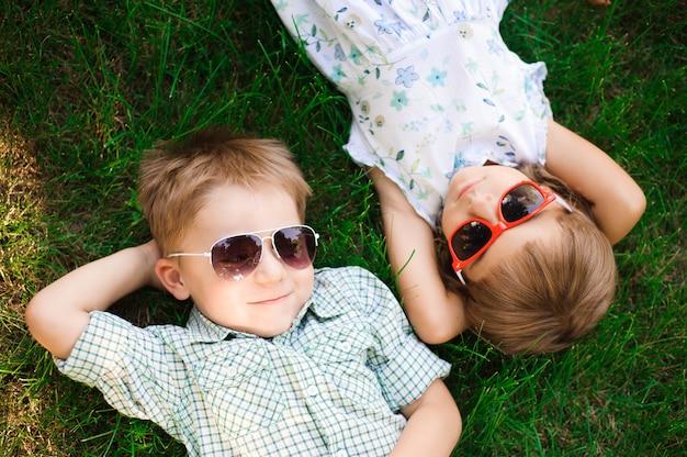 Bambini sorridenti al giardino in occhiali da sole