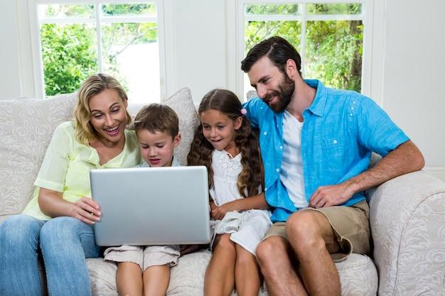 Bambini sorridenti con i genitori che per mezzo del computer portatile a casa