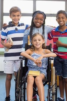 Bambini sorridenti della scuola che stanno con il braccio intorno in biblioteca