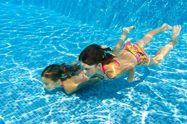 Bambini sorridenti felici sott'acqua in piscina, belle ragazze nuotano e si divertono. sport per bambini in vacanza estiva in famiglia. vacanza attiva