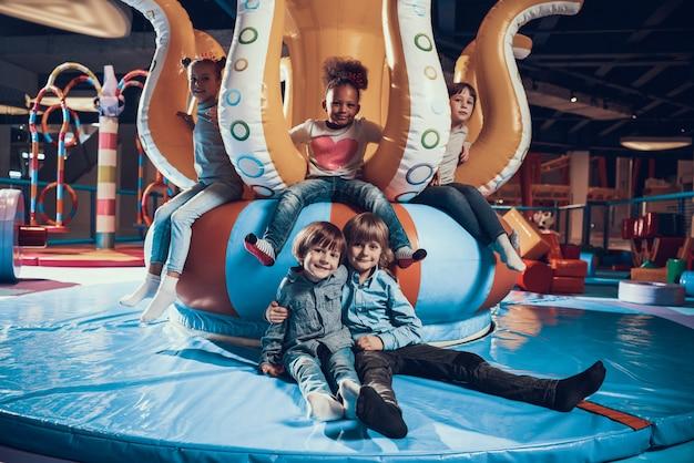 Bambini sorridenti svegli sul moderno parco giochi al coperto