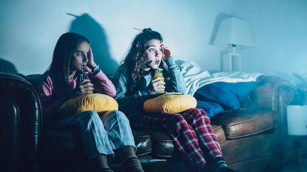 Bambini spaventati con succo guardando la tv