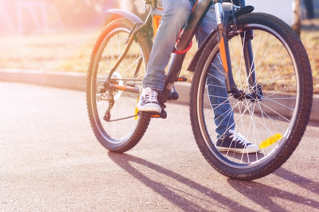 Bambini su una bicicletta sulla strada asfaltata nel primo mattino d'estate.