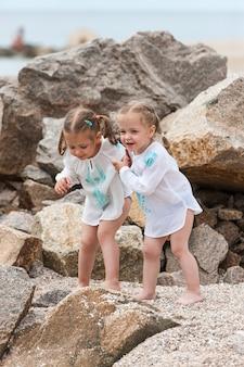 Bambini sulla spiaggia del mare. gemelli in piedi contro pietre e acqua di mare.