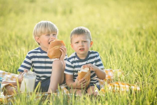 Bambini svegli che bevono latte e che mangiano pane