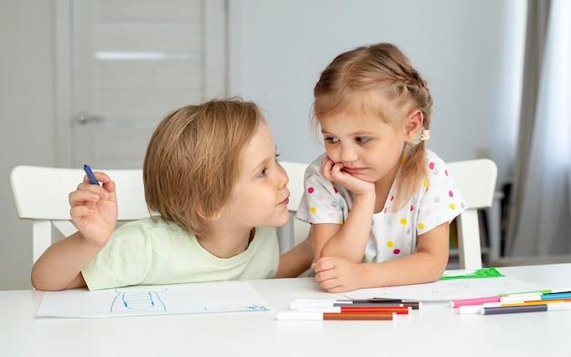 Bambini svegli che giocano mentre disegnano