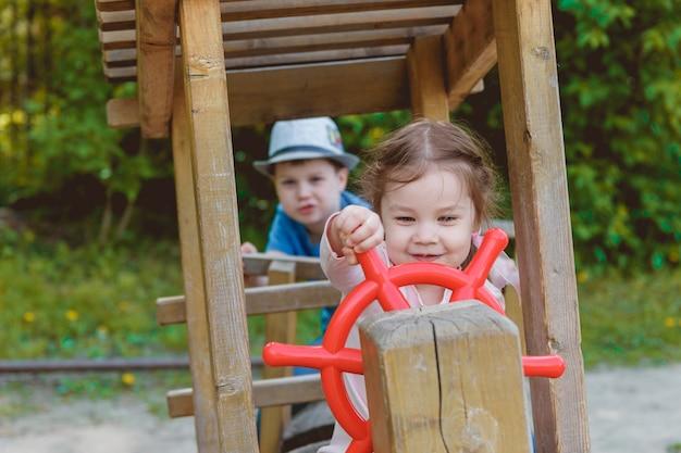 Bambini svegli che giocano nel parco