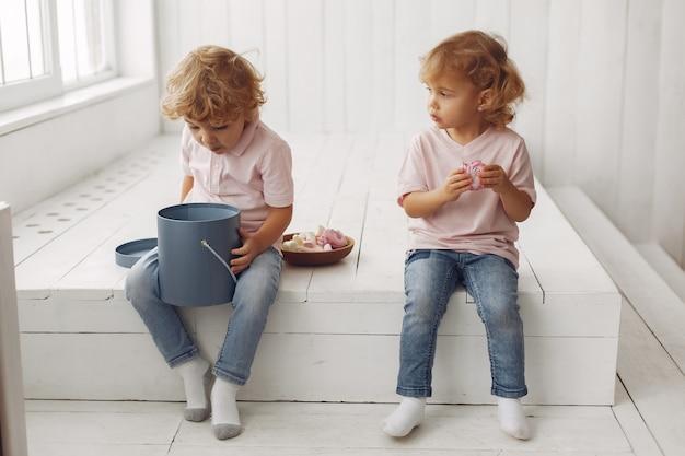 Bambini svegli che mangiano i biscotti a casa