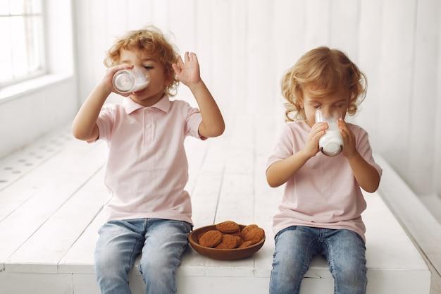 Bambini svegli che mangiano i biscotti e che bevono latte