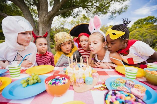 Bambini svegli che saltano insieme sulla candela durante una festa di compleanno