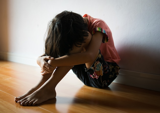 Bambini tristi, ragazza che si siede da solo nell'angolo a casa