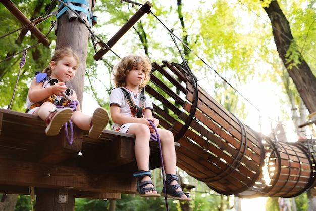 Bambini - un ragazzo e una ragazza nel parco delle funi passano ostacoli