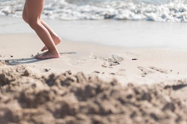 Bambino a piedi nudi che gioca in riva al mare