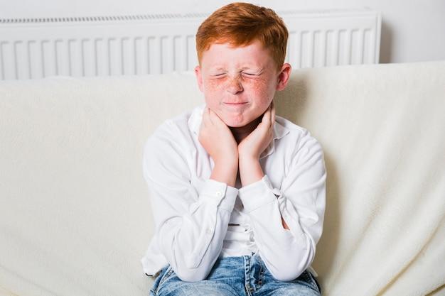 Bambino a tiro medio che avverte mal di gola