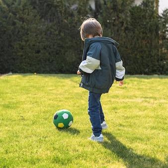 Bambino a tutto campo che gioca con la palla