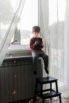 Bambino a tutto campo che si siede con il tablet