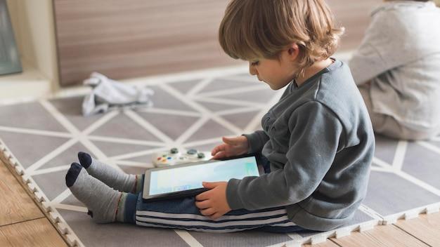 Bambino a tutto campo con tablet al chiuso