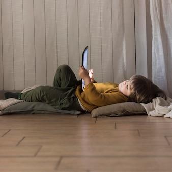 Bambino a tutto campo sul pavimento con il tablet