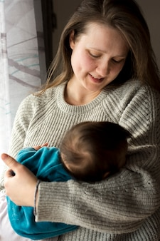Bambino addormentato della holding della donna in armi