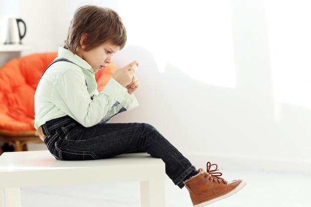Bambino adorabile che gioca con uno smartphone