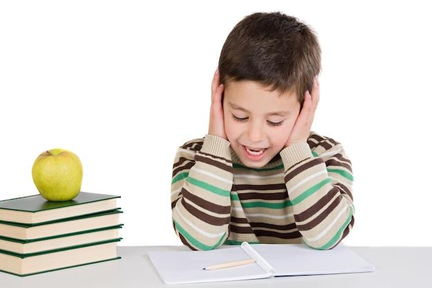 Bambino adorabile che studia con i libri e la mela su una priorità bassa eccessiva bianca