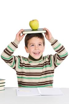 Bambino adorabile che studia con i libri e mela nella testa un fondo bianco eccessivo
