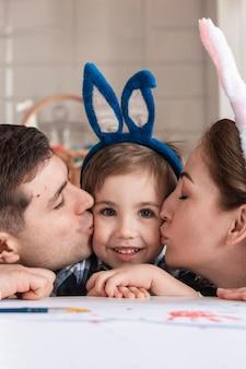 Bambino adorabile del primo piano che è baciato dalla madre e dal padre