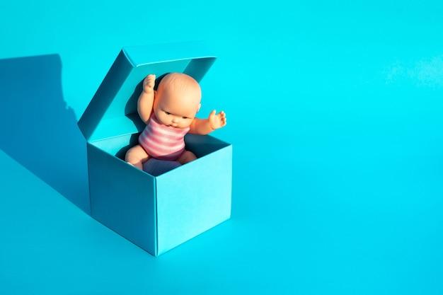 Bambino all'interno di una scatola su sfondo blu