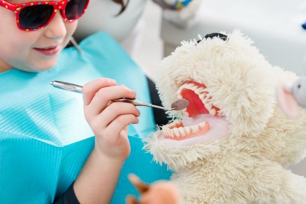 Bambino all'ufficio del dentista che si occupa dei denti del giocattolo dell'animale domestico