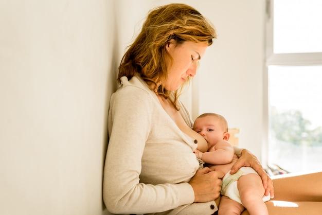 Bambino allattato al seno per latte materno, concetto di maternità alternativo