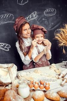 Bambino allegro con la madre che produce pasta