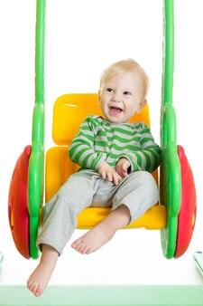 Bambino allegro del bambino che gioca sull'oscillazione