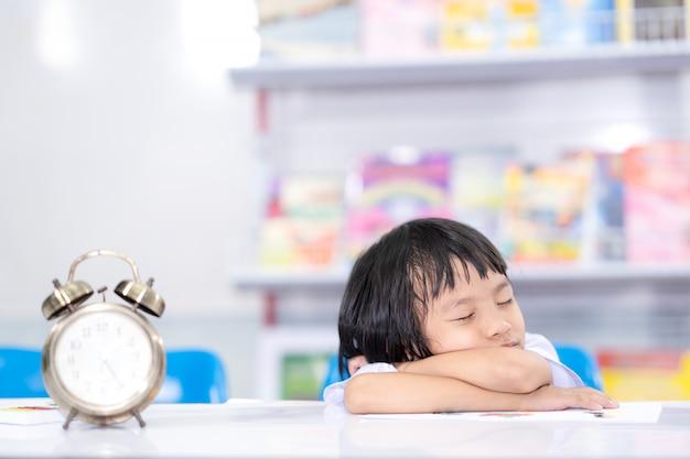 Bambino annoiato impara e studia per dormire sul tavolo