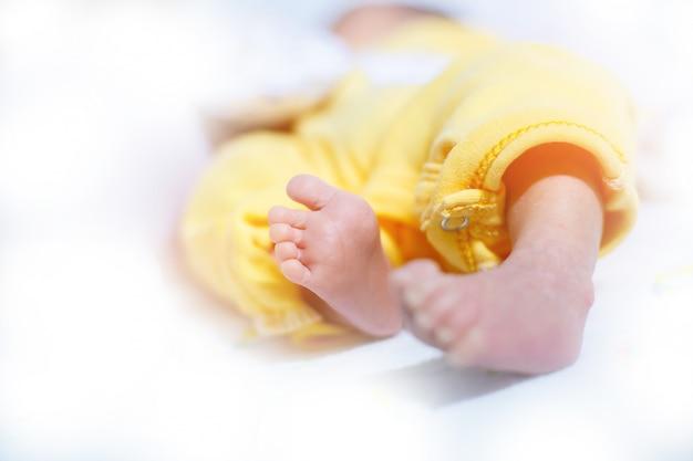 Bambino appena nato del piede, fuoco selettivo e molle su fondo bianco.