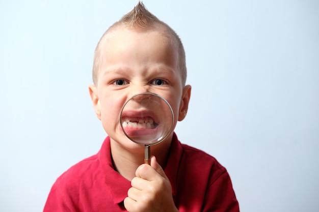 Bambino arrabbiato che mostra i denti (sorriso) attraverso la lente di ingrandimento