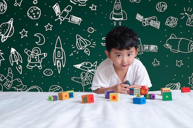 Bambino asiatico che gioca giocattolo con l'avventura dello spazio e di scienza, fondo disegnato a mano