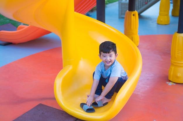 Bambino asiatico che gioca scorrevole al campo da giuoco sotto la luce solare di estate