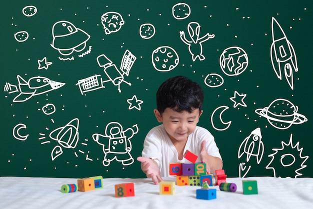 Bambino asiatico che impara giocando con la sua immaginazione sulla scienza e l'avventura spaziale