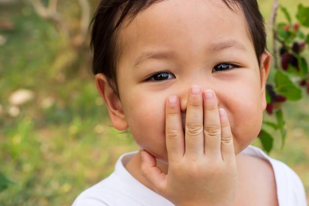 Bambino asiatico che ride gag. primo piano nei suoi occhi. sentirsi felici.