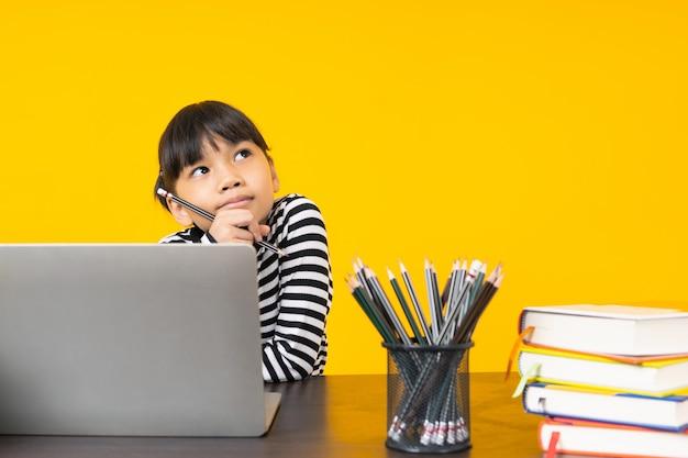 Bambino asiatico che si siede e che pensa con il computer portatile e la tavola