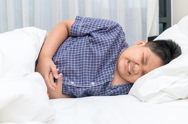 Bambino asiatico che soffre di mal di stomaco e sdraiato sul letto.