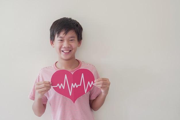 Bambino asiatico che tiene grande cuore rosso con cardiogramma
