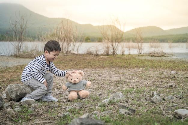 Bambino asiatico con orsacchiotto seduto sito il serbatoio è lo sfondo