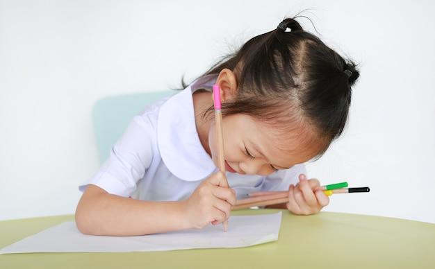 Bambino asiatico in uniforme scolastico con scrittura a matita sul tavolo isolato su priorità bassa bianca.