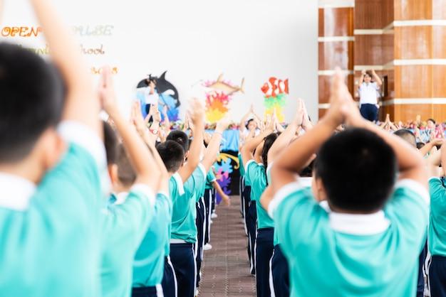 Bambino asiatico stare in linea ed esercitare all'aperto. attività fisica del bambino a scuola