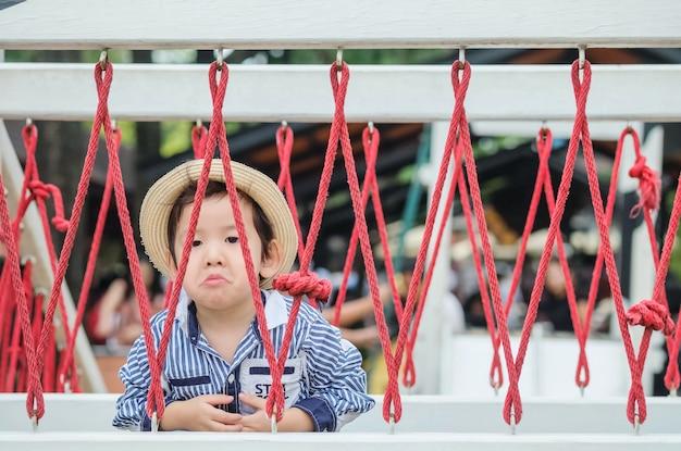 Bambino asiatico sveglio del primo piano con il fronte annoiato su un ponte nel fondo del campo da giuoco
