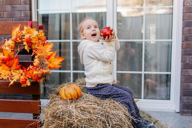 Bambino bambino in giacca di maglia bianca seduto sul pagliaio con zucche sotto il portico e giocando con la mela.