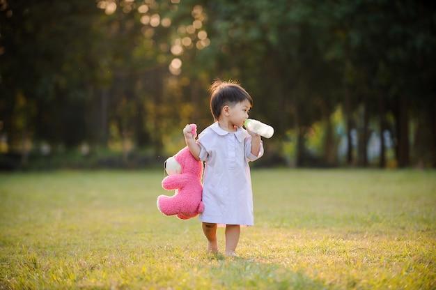 Bambino bambino rilassante in giardino e bere latte dalla bottiglia.